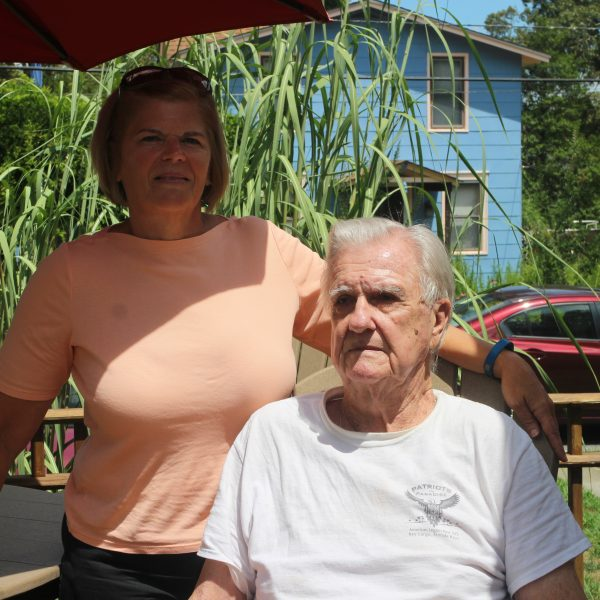 Proudly smiling towards the camera, an adult woman and her senior father enjoy summer weather on their porch.