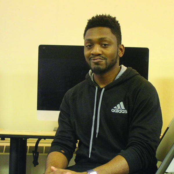Smiling towards the camera, a young man with hopes of becoming an IT professional sits in a computer lab.