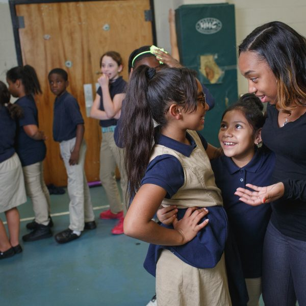 Two young female students look up to their teacher in a school gym, while their classmate line up behind them.