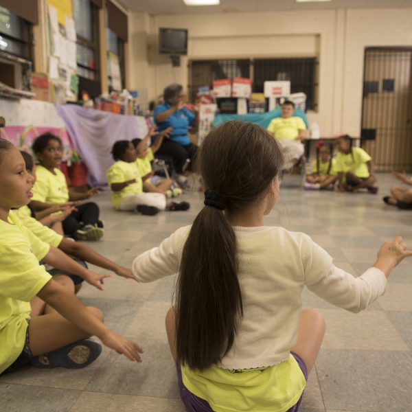 A group of second graders sit in a circle and play a game of Duck-Duck-Goose.