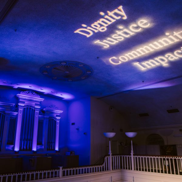 """The words """"dignity,"""" """"justice,"""" """"community,"""" and """"impact,"""" are projected onto a high ceiling."""
