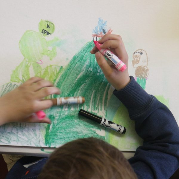 young boy with markers draws picture of landscape and monsters.